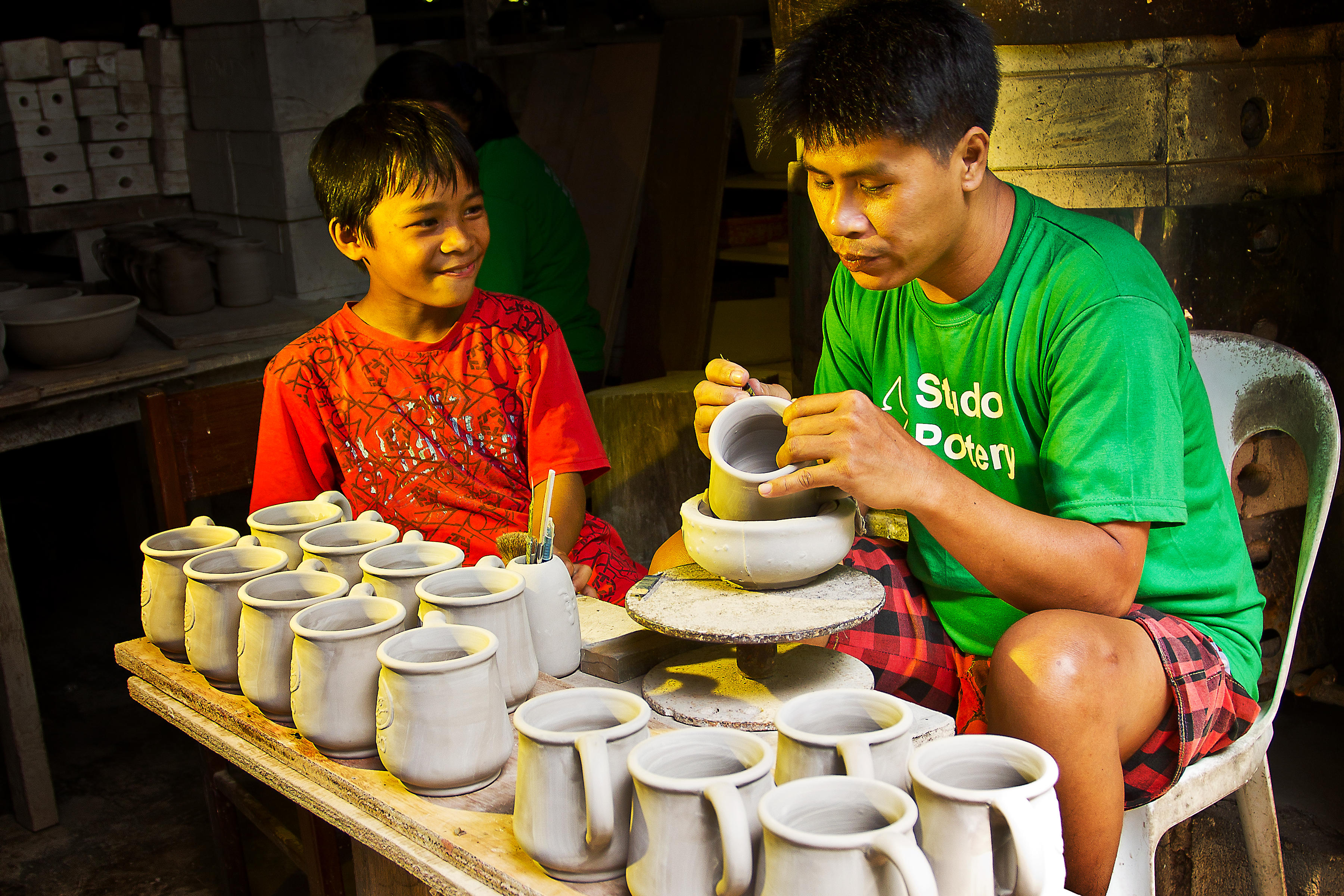 A father in the Philippines teaches his son the basics of pottery. © 2012 Kai, Courtesy of Photoshare